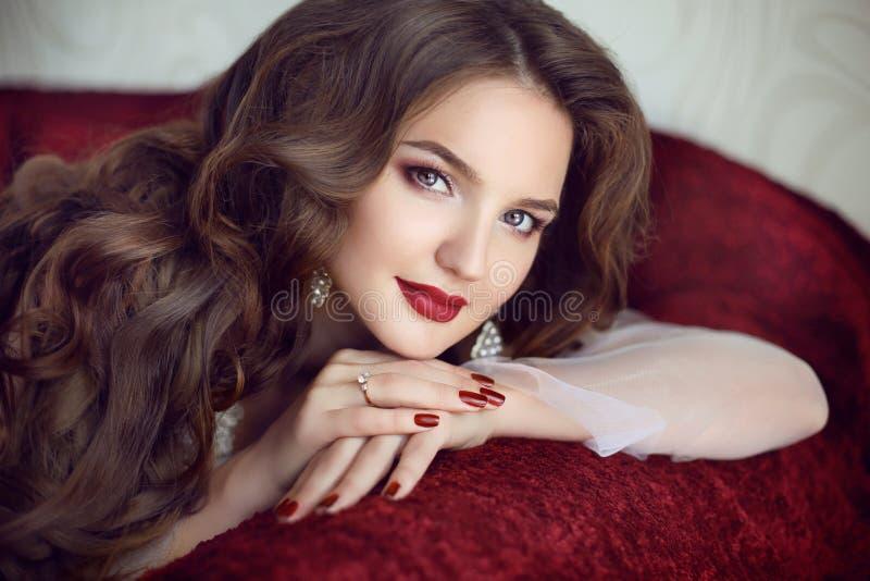 Mooie donkerbruine bruidvrouw Huwelijksmake-up Het rood manicured Na stock fotografie