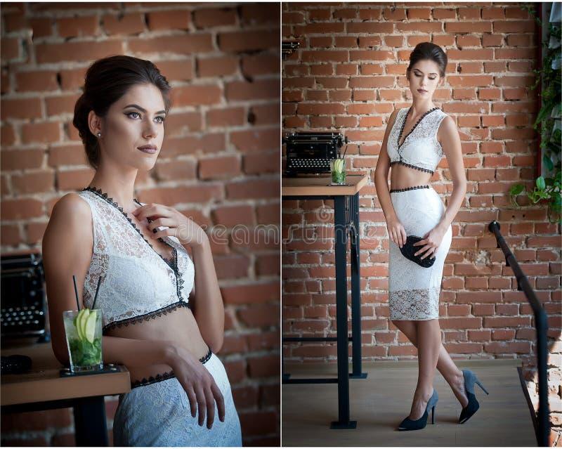 Mooie donkerbruine dame in elegante witte twee stukken uitrusting het stellen in een uitstekende scène stock fotografie