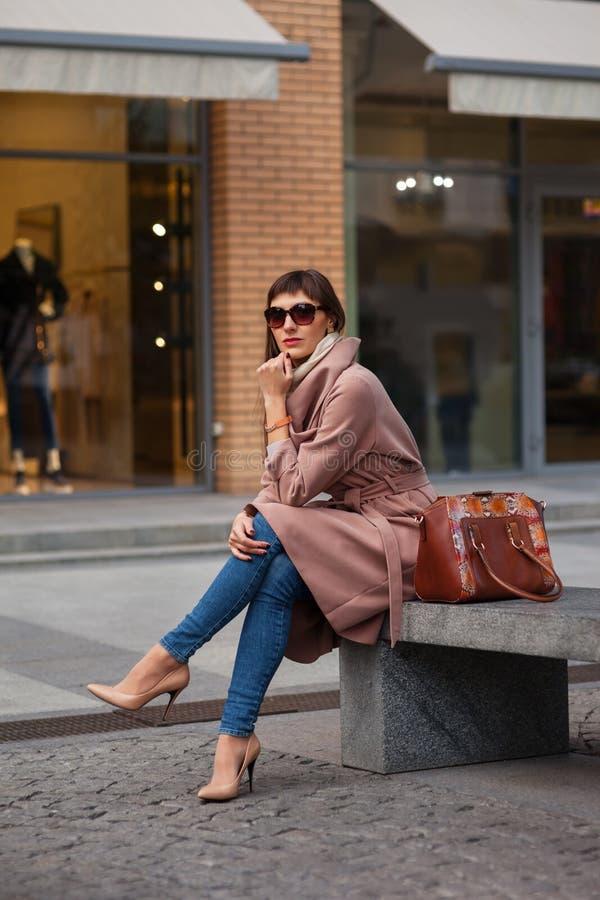 Mooie donkerbruine jonge vrouw in aardige bruine beige laag, jeans en zonnebril De schoenen van vrouwen op hoge ge?soleerdew hiel stock foto's