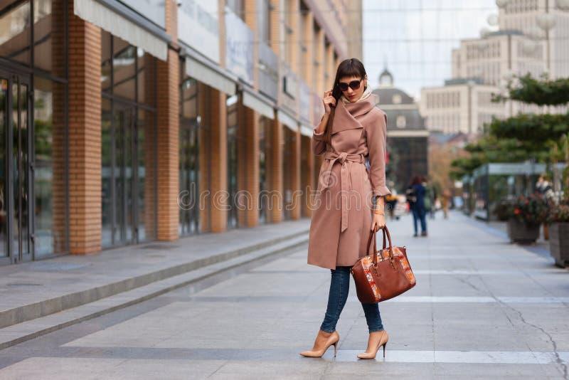 Mooie donkerbruine jonge vrouw in aardige bruine beige laag, jeans en zonnebril De schoenen van vrouwen op hoge ge?soleerdew hiel royalty-vrije stock afbeeldingen
