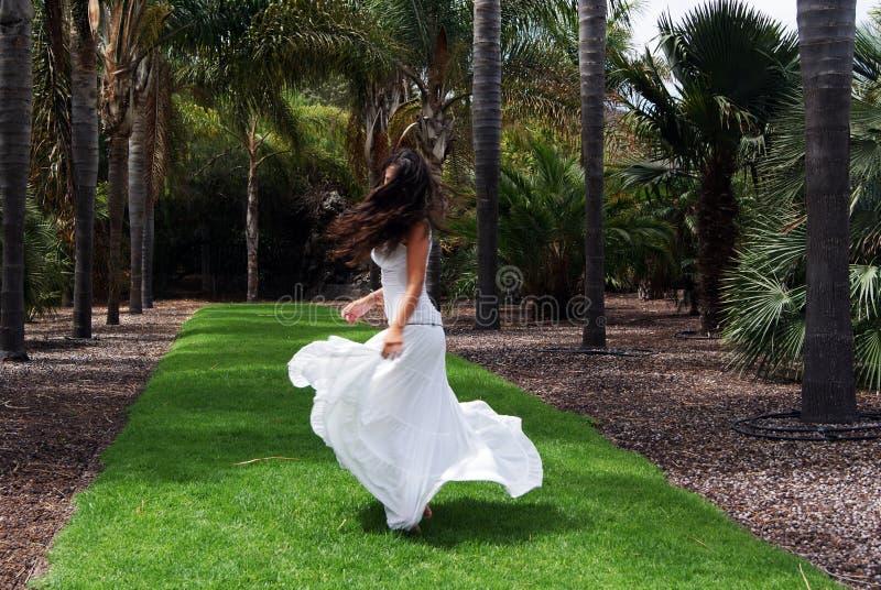Mooie donkerbruine jonge vrouw die in aard met een lange witte kleding dansen royalty-vrije stock fotografie