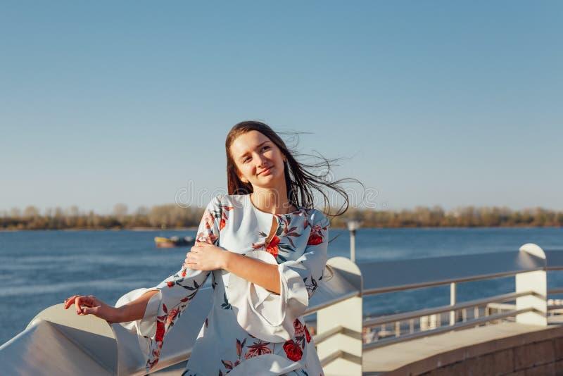 Mooie donkerbruine jonge vrouw die in blauwe kleding van zonsopgang genieten door het overzees royalty-vrije stock afbeelding
