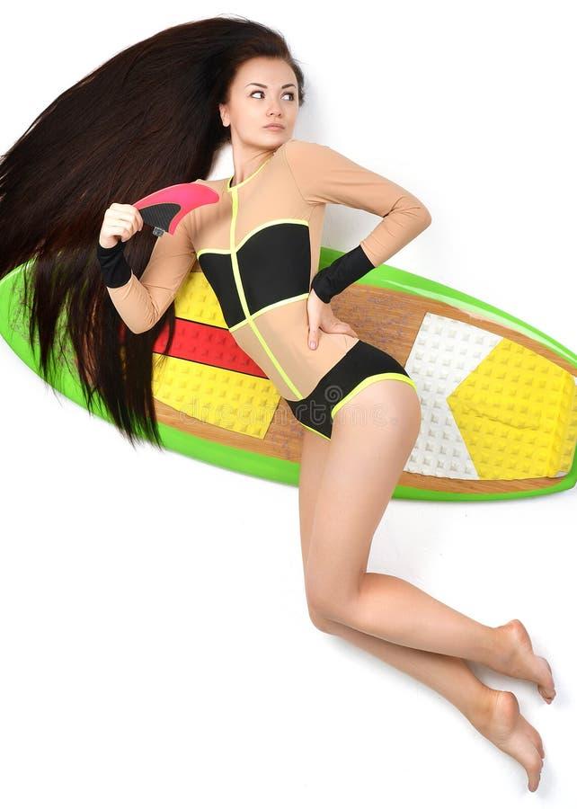 Mooie donkerbruine jonge vrouw die op lange surfplankraad liggen royalty-vrije stock afbeeldingen