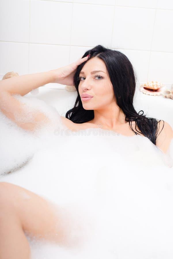 Mooie donkerbruine jonge vrouw met blauwe ogen die in het bad met schuim liggen die de camera op lichte exemplaar ruimteachtergro stock afbeelding