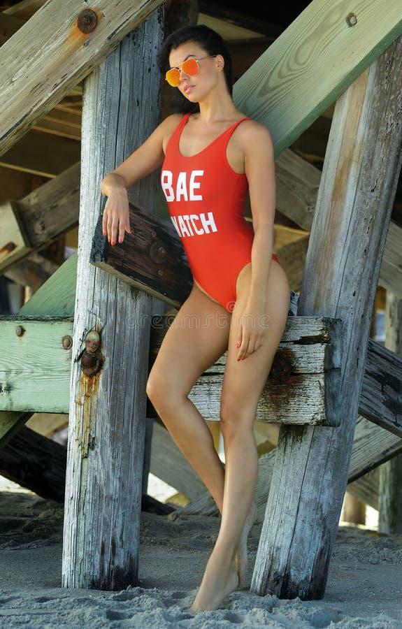 Mooie donkerbruine jonge vrouw met perfect sexy geschikt lichaam in het rode zwempak stellen op het strand stock foto