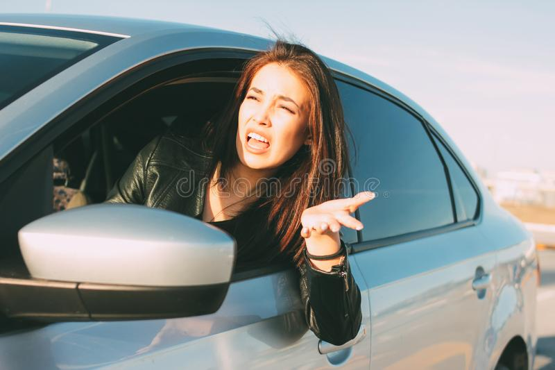 Mooie donkerbruine lange haar boze jonge Aziatische vrouw die en in auto drijven gillen stock afbeelding