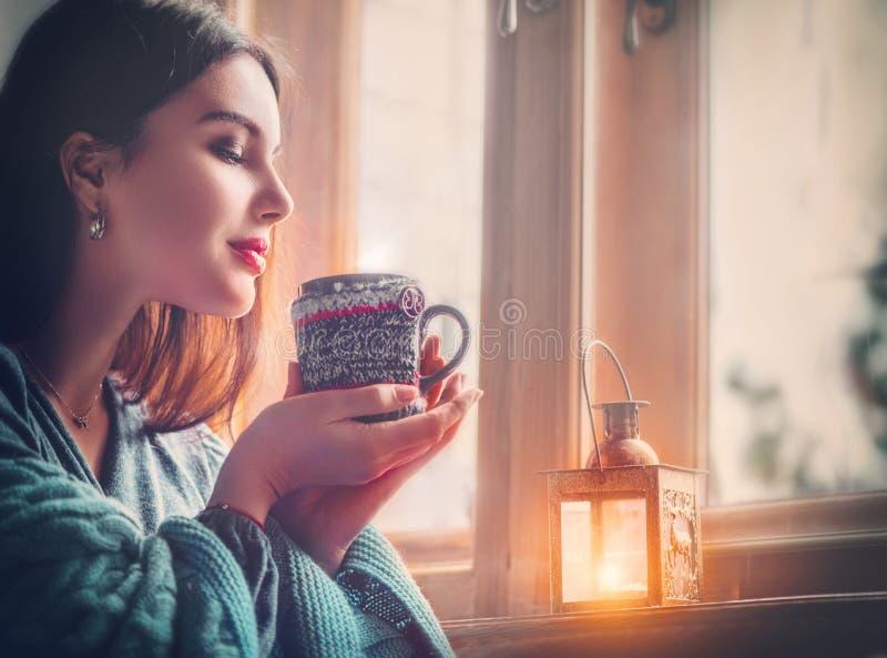 Mooie donkerbruine meisje het drinken koffie die thuis, uit het venster kijken Schoonheids modelvrouw met kop van hete thee royalty-vrije stock afbeeldingen