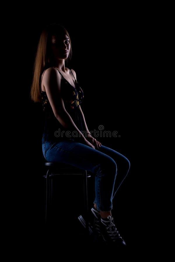 Mooie donkerbruine meisjeszitting op een barstoel royalty-vrije stock fotografie