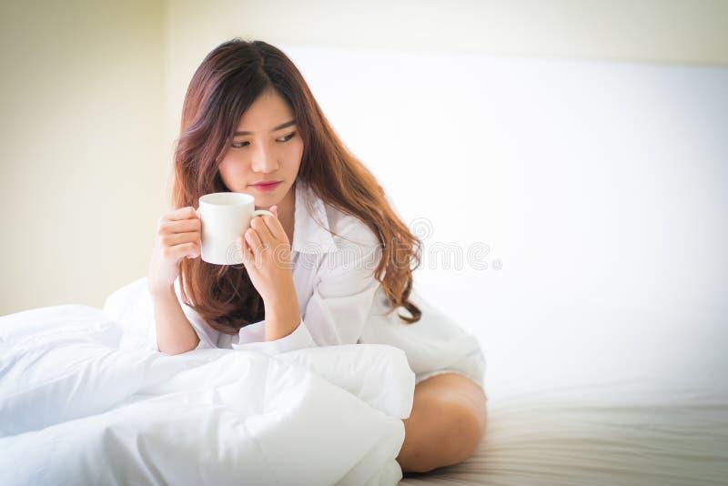 Mooie donkerbruine van de vrouwen het drinken en ochtend koffie in slaapkamer royalty-vrije stock afbeeldingen