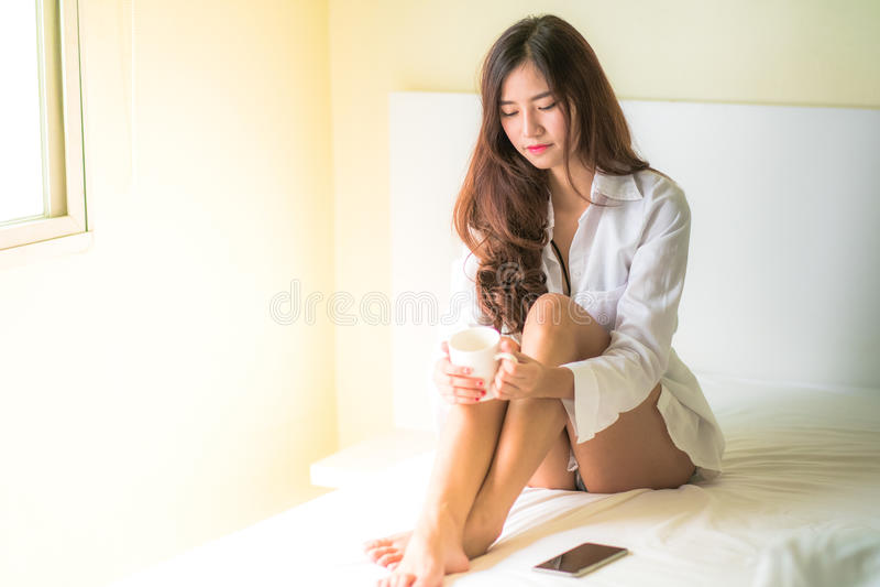 Mooie donkerbruine van de vrouwen het drinken en ochtend koffie in slaapkamer royalty-vrije stock fotografie