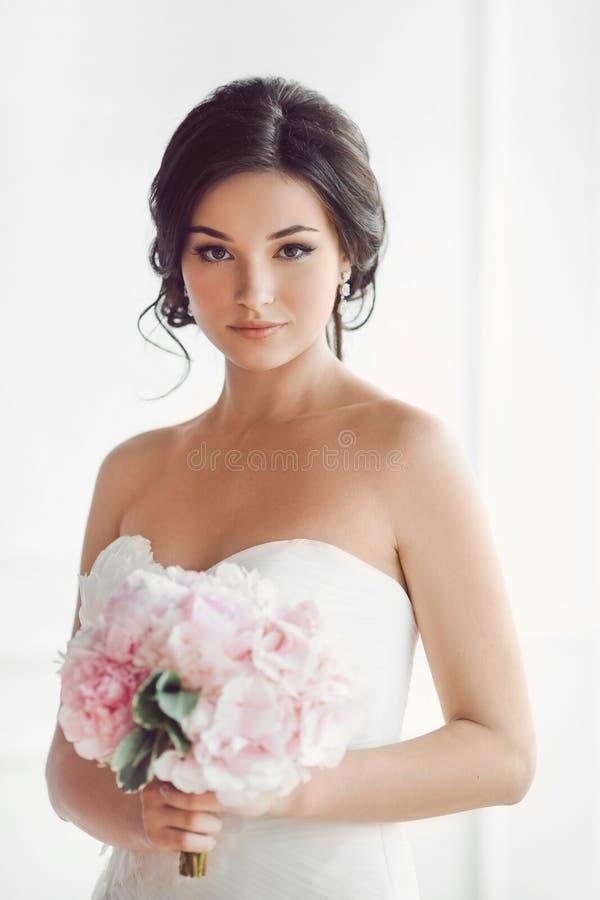 Mooie donkerbruine vrouw als bruid met roze huwelijksboeket op wit royalty-vrije stock foto's