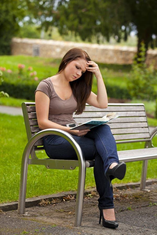 Mooie donkerbruine vrouw die een boek leest royalty-vrije stock foto
