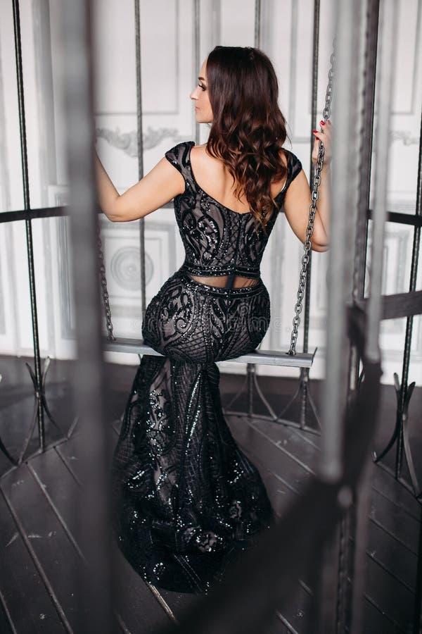 Mooie donkerbruine vrouw die het glanzende zwarte kleding stellen in kooi zoals vogel dragen royalty-vrije stock fotografie