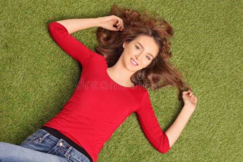 Mooie donkerbruine vrouw die op gras liggen stock fotografie