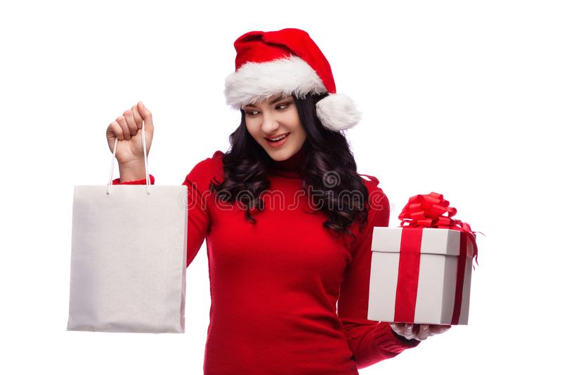 Mooie donkerbruine vrouw die santahoed dragen en giftdoos en het winkelen zak houden Geïsoleerde royalty-vrije stock afbeeldingen