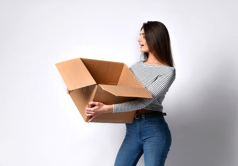Mooie donkerbruine vrouw die zich op een lichte achtergrond met een bewegende kartondoos bevinden stock afbeeldingen