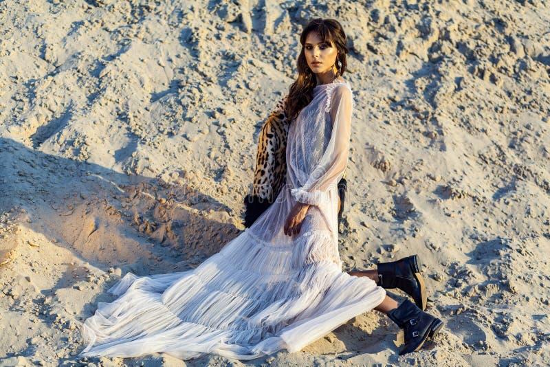 Mooie donkerbruine vrouw in doorzichtige stranddekking omhoog met luipaardbontjas en zwarte laarzen die op zandig strand bij zons royalty-vrije stock foto