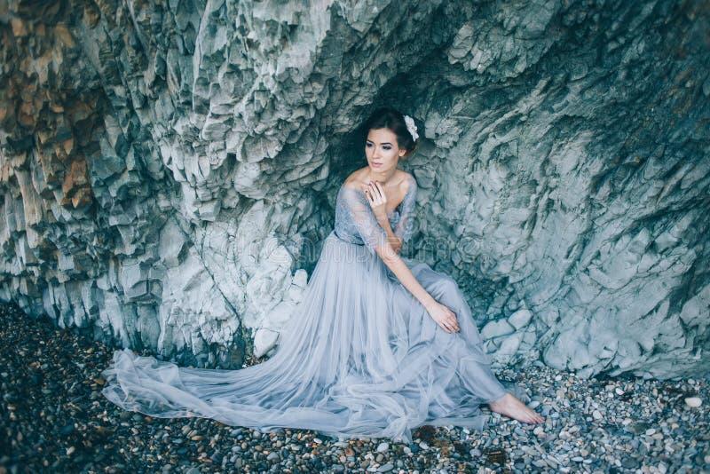 Mooie donkerbruine vrouw in een lange huwelijkskleding op het strand stock fotografie
