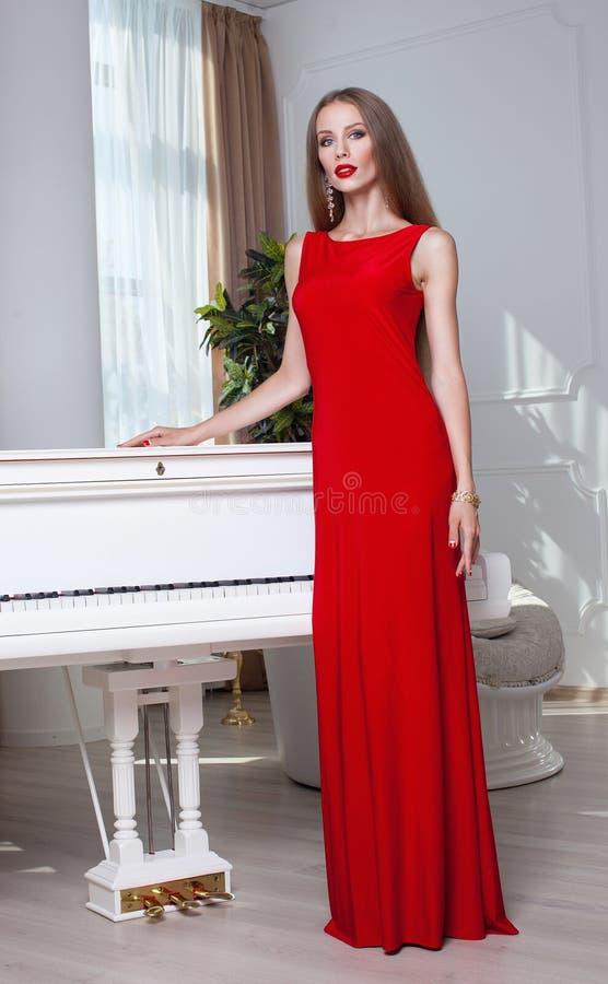 Mooie donkerbruine vrouw in een rode kleding Het schot van de studio Lang haar Rode Lippen stock foto's