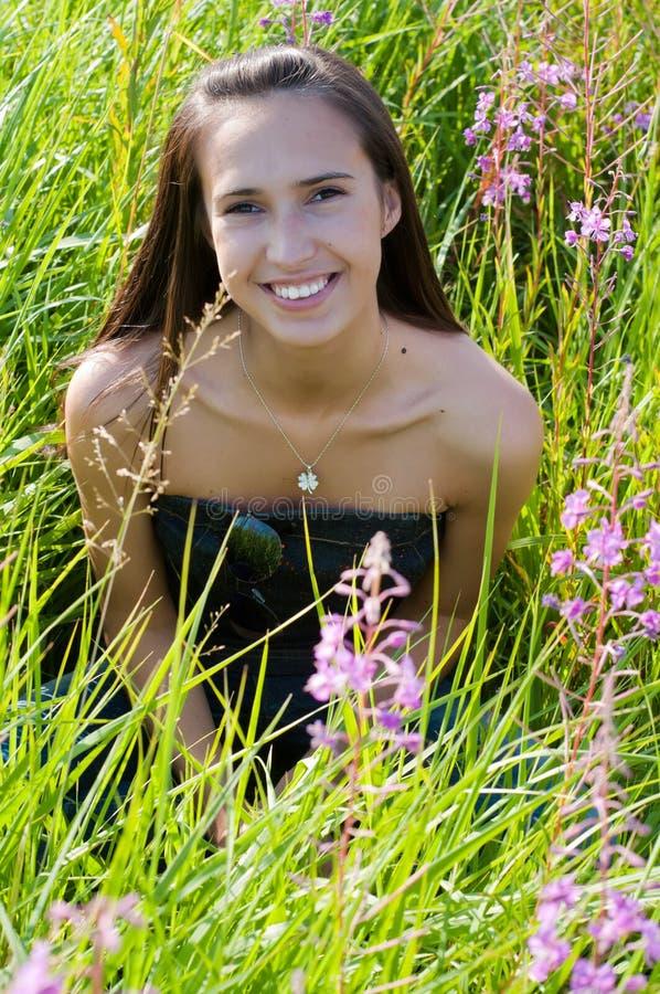 Mooie donkerbruine vrouw in gras royalty-vrije stock foto