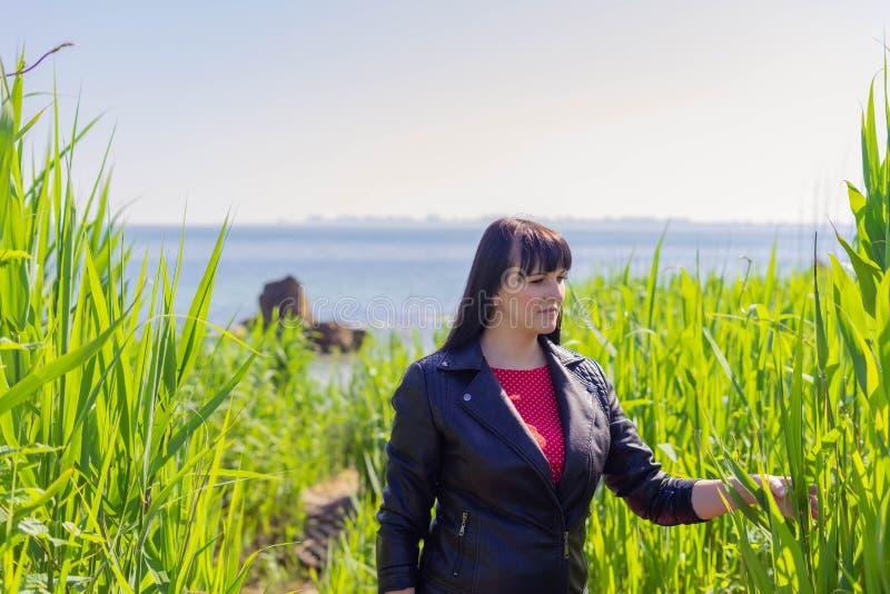 Mooie donkerbruine vrouw in het rode kleding stellen tegen de achtergrond van het overzees op een zonnige de lentedag stock afbeeldingen