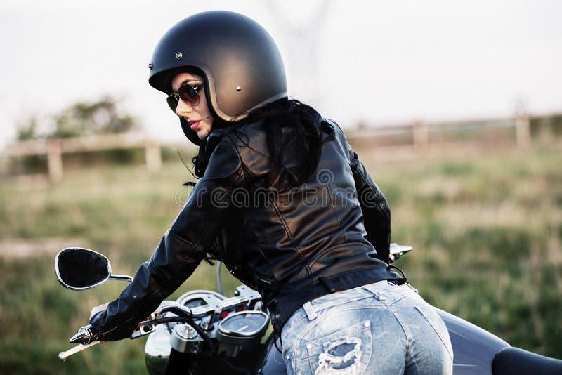 Mooie donkerbruine vrouw met een klassieke motorfiets c stock afbeelding