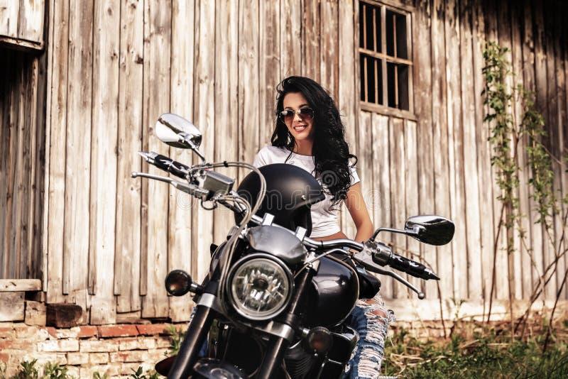 Mooie donkerbruine vrouw met een klassieke motorfiets c royalty-vrije stock afbeeldingen