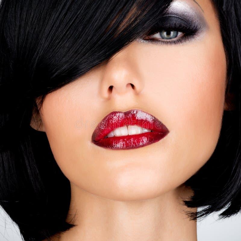 Mooie donkerbruine vrouw met geschoten kapsel en sexy rode lippen stock afbeelding