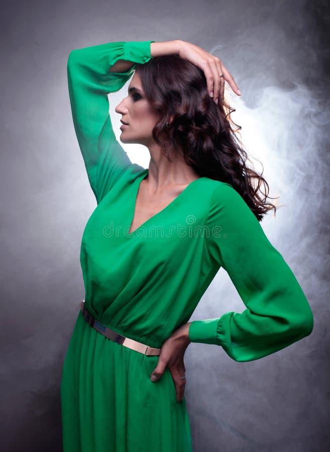 Mooie donkerbruine vrouw met krullend lang haar in groene kleding stock fotografie