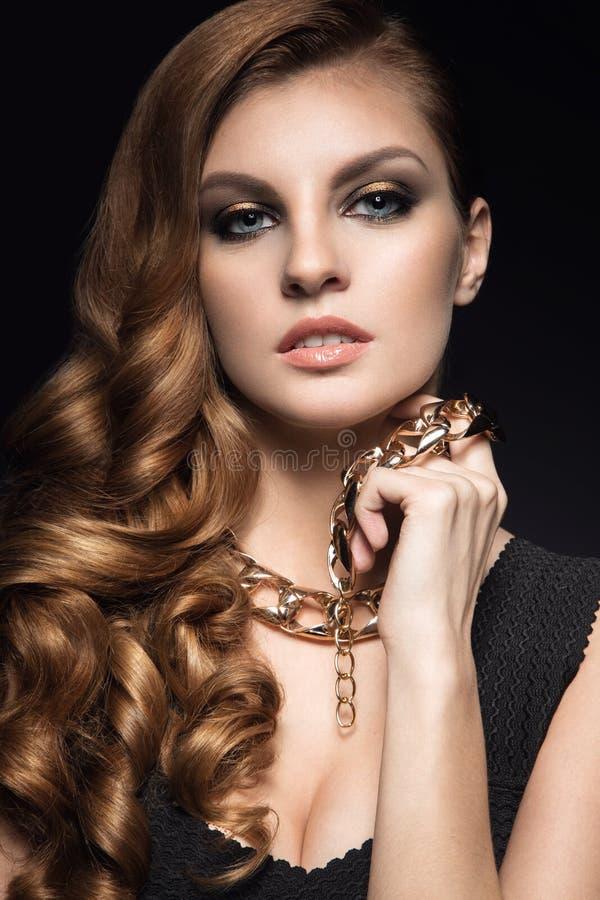 Mooie donkerbruine vrouw met perfecte huid, heldere make-up en gouden juwelen Het Gezicht van de schoonheid stock foto