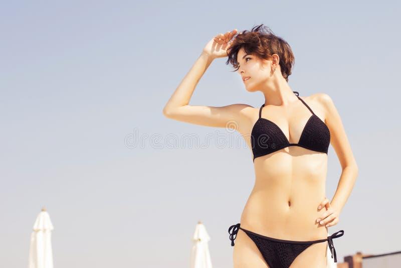 Mooie donkerbruine vrouw op het strand in pool het alleen binnen ontspannen royalty-vrije stock foto's