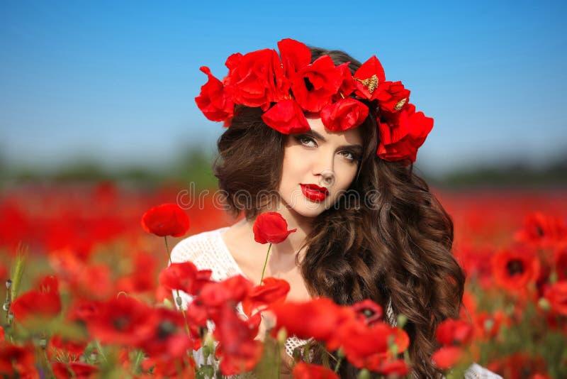 Mooie donkerbruine vrouw op papaversgebied met bloemen, attracti stock fotografie