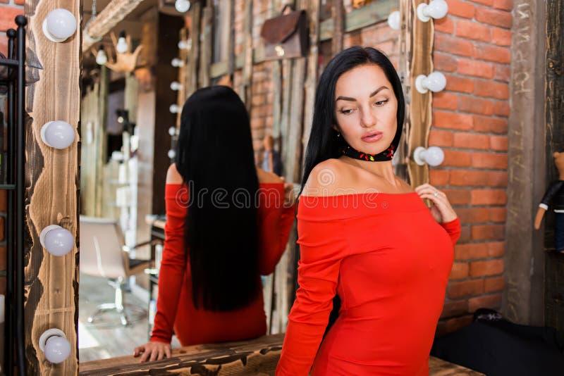 Mooie donkerbruine vrouw in rode kleding dichtbij spiegel Manier, schoonheid, zorg royalty-vrije stock foto