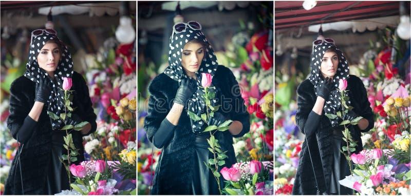 Mooie donkerbruine vrouw in zwarte bij bloemistwinkel stock afbeelding