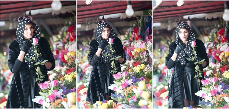 Mooie donkerbruine vrouw in zwarte bij bloemistwinkel royalty-vrije stock foto's