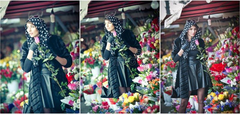 Mooie donkerbruine vrouw in zwarte bij bloemistwinkel stock afbeeldingen