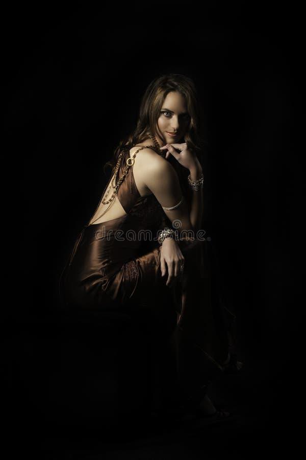 Mooie donkerbruine zitting die avondjurk en juwelen uitputten stock afbeeldingen