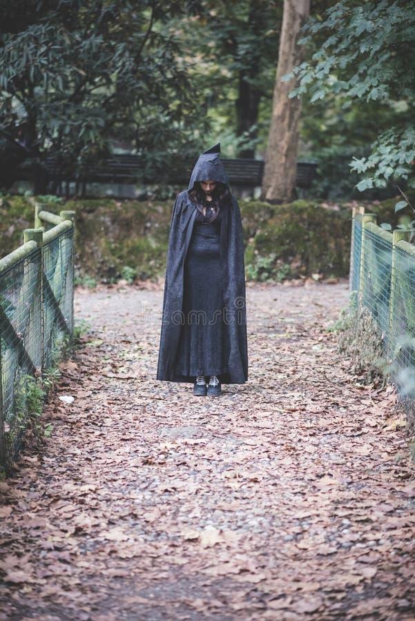 Mooie donkere vampiervrouw met zwarte mantel en kap stock afbeelding