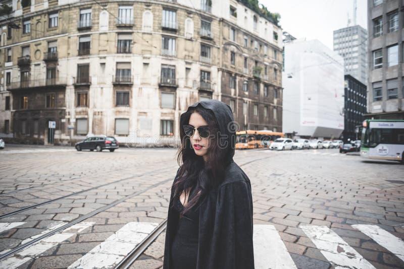 Mooie donkere vampiervrouw met zwarte mantel en kap stock fotografie