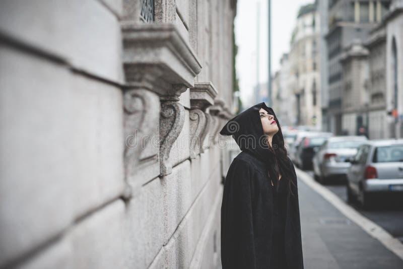 Mooie donkere vampiervrouw met zwarte mantel en kap royalty-vrije stock afbeeldingen