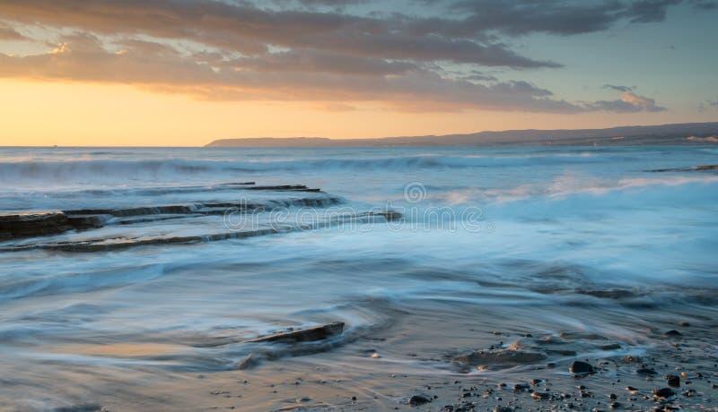 Mooie dramatische Zonsondergang over een rotsachtige kust royalty-vrije stock foto