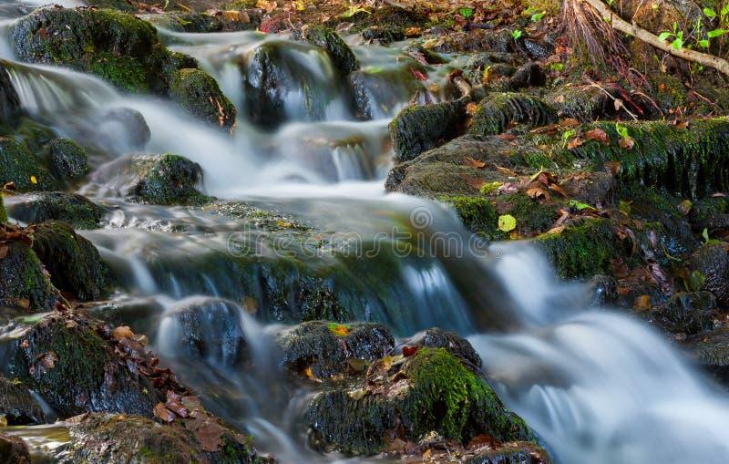 Mooie draperende waterval over natuurlijke rotsen stock afbeelding
