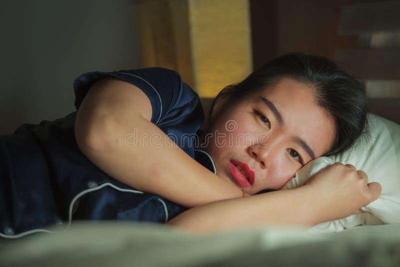 Mooie droevige en gedeprimeerde Aziatische Koreaanse vrouw wakker in bed laat - nacht die bezorgdheids aan crisis en het gevoel v royalty-vrije stock fotografie