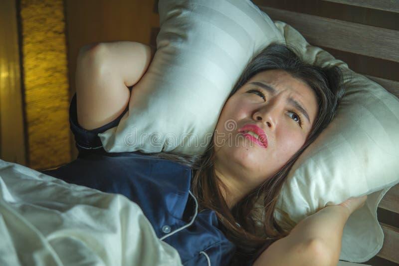 Mooie droevige en gedeprimeerde Aziatische Koreaanse vrouw wakker in bed laat - nacht die bezorgdheids aan crisis en het gevoel v royalty-vrije stock foto