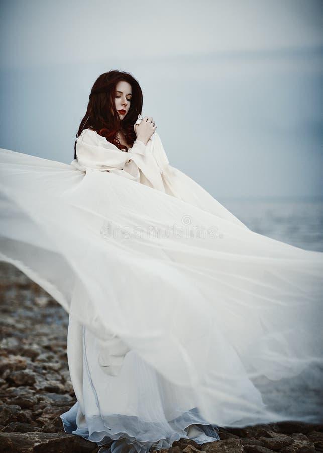 Mooie droevige jonge vrouw in witte kleding die zich op overzees strand bevinden royalty-vrije stock afbeelding
