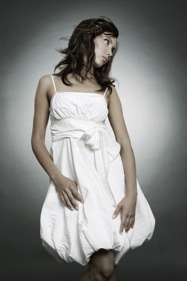 Mooie droevige vrouw die in kleding iets bekijkt stock fotografie