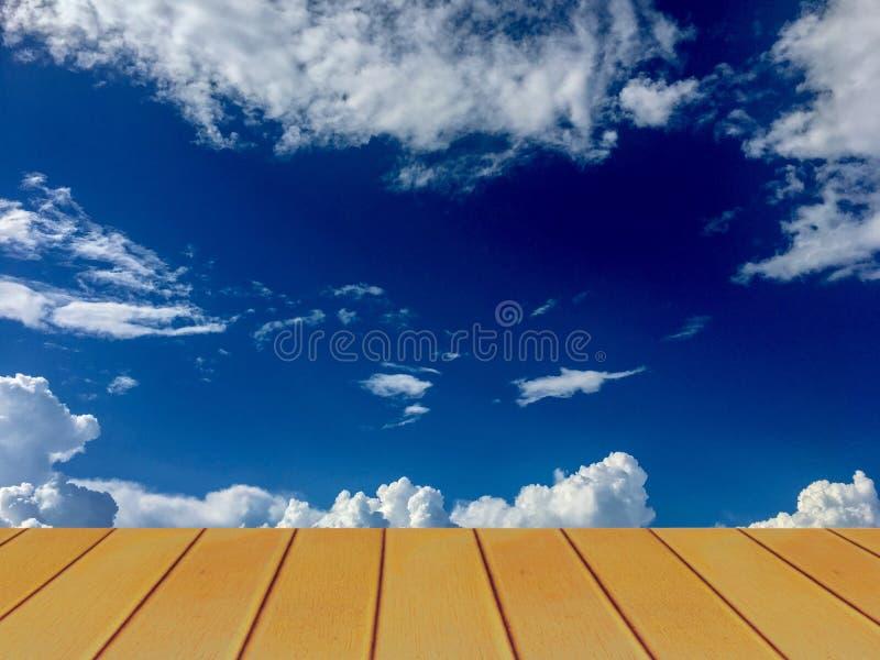 Mooie duidelijke blauwe hemel en witte wolk erachter van houten terras stock foto's