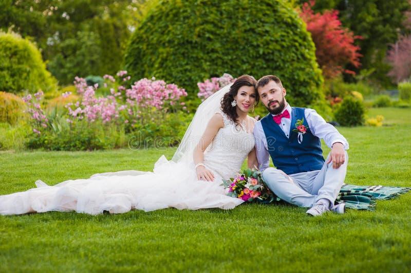 Mooie echtpaarzitting op het gras royalty-vrije stock foto's