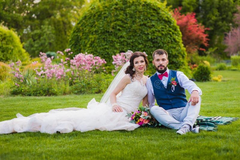 Mooie echtpaarzitting op het gras in park bij hun huwelijksdag stock foto's
