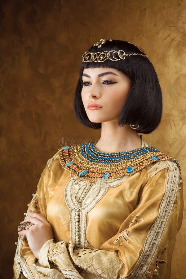 Mooie Egyptische vrouw zoals Cleopatra op gouden achtergrond stock afbeeldingen
